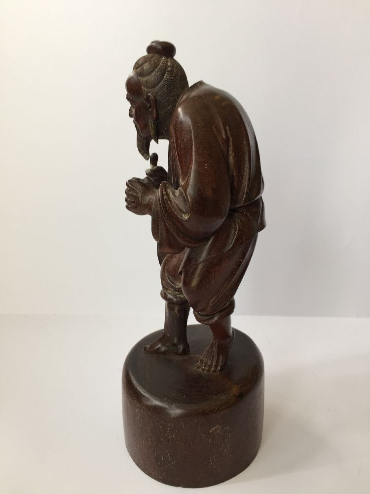 A Chinese carved hardwood figure of a fisherman, 20th century, carved clutching a fish in his - Image 2 of 6