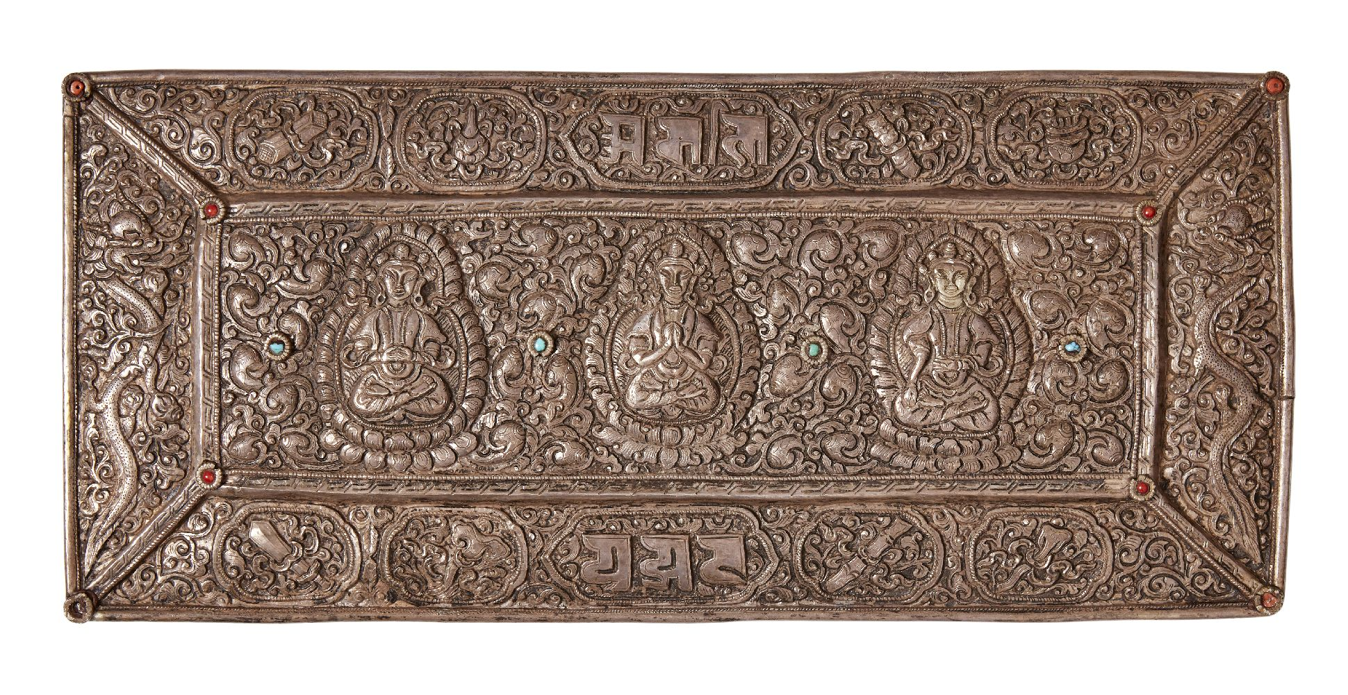 A Tibetan repousse white metal plaque, early 20th century, of rectangular form, decorated to the
