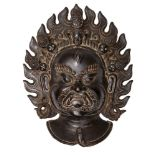 A Tibetan bronze plaque of Mahakala, 19th century, cast with flame halo, loose earrings, and serpent