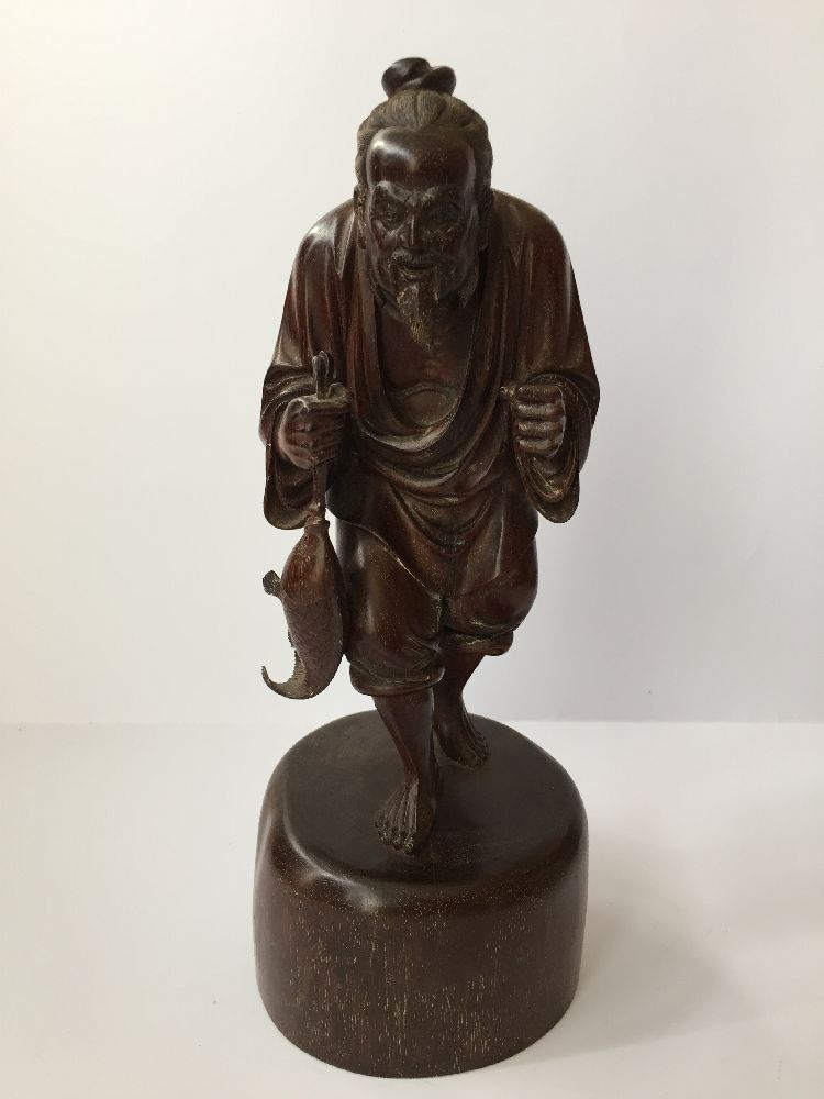 A Chinese carved hardwood figure of a fisherman, 20th century, carved clutching a fish in his - Image 6 of 6