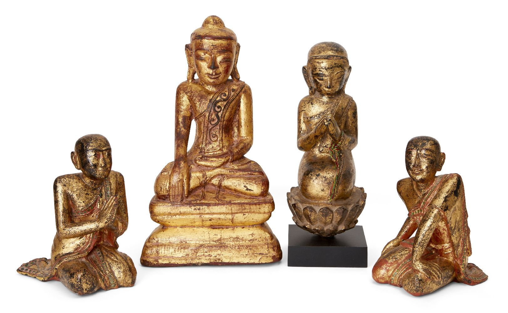 Four Thai giltwood buddhas, late 19th - early 20th century, one kneeling in prayer on a lotus