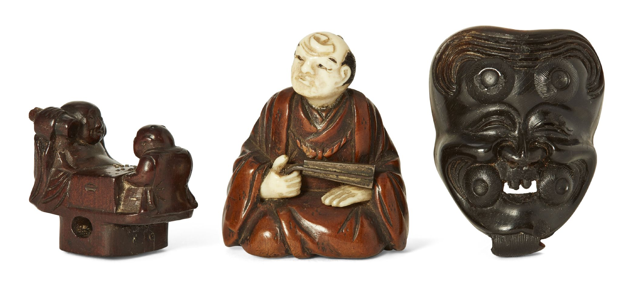 Three Japanese wood netsuke, 19th century, carved as Hotei and Karako playing Go; an Okina Noh mask;