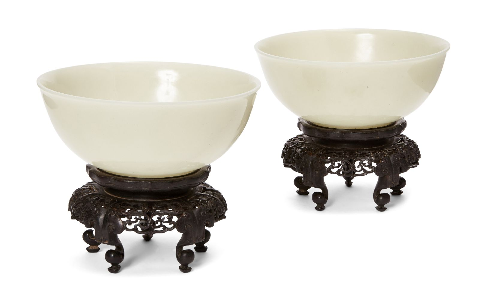 A pair of Chinese pale celadon jade bowls, 19th century, each carved with deep sides and a