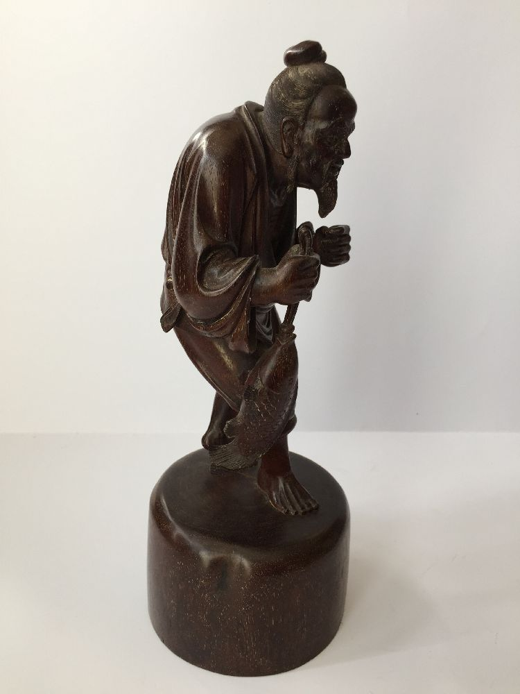 A Chinese carved hardwood figure of a fisherman, 20th century, carved clutching a fish in his - Image 4 of 6