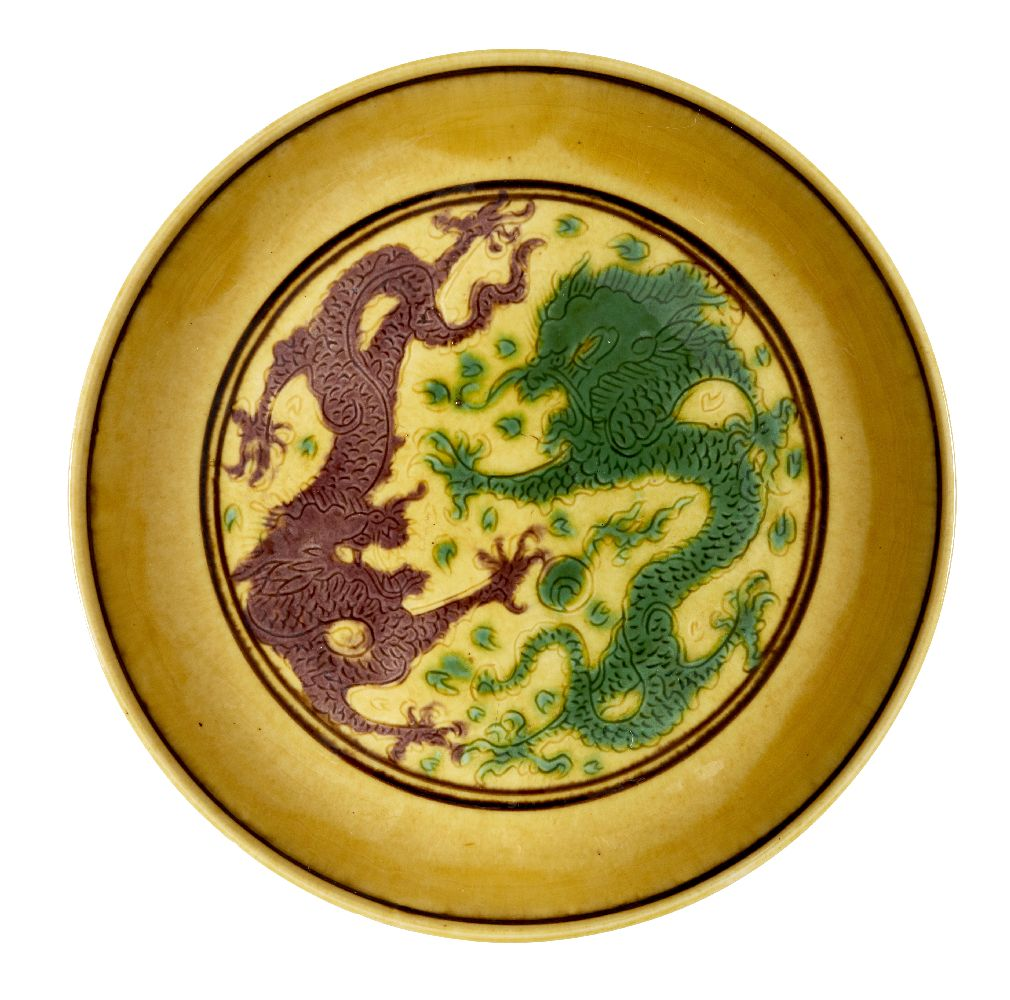 A Chinese yellow-ground aubergine and green-decorated saucer dish, Kangxi mark and of the period,
