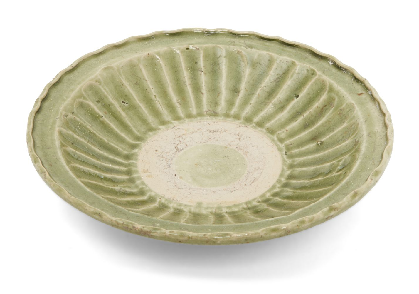 A Vietnamese stoneware green-glazed dish, 14th century, with pinched petal design to the interior