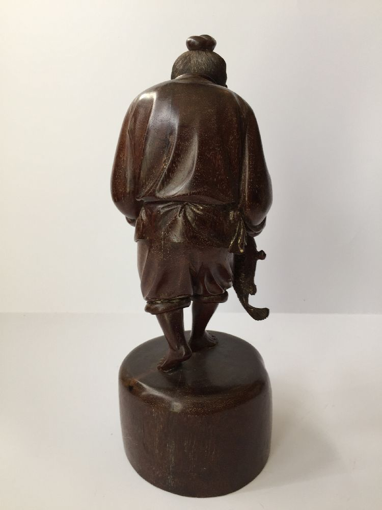 A Chinese carved hardwood figure of a fisherman, 20th century, carved clutching a fish in his - Image 3 of 6