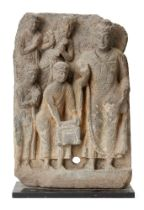 A Gandhara grey schist frieze, 2nd-3rd century, depicting Buddha with adorants, on a metal plinth,
