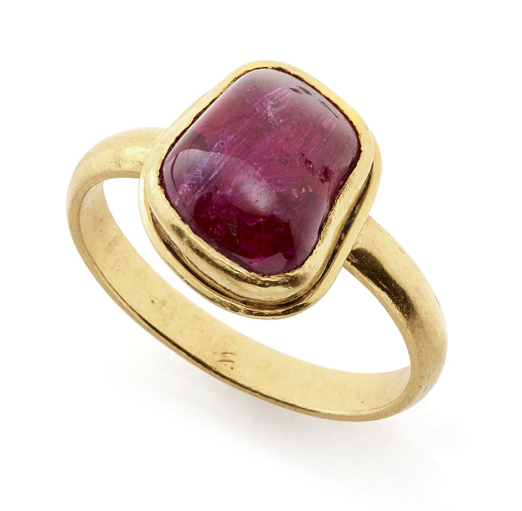 A ruby-set gold ring, South India, in a modern gold setting, the polished pebble stone of almost