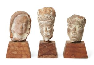 Three small sandstone carved heads, Gupta period, India, 3rd-4th century AD, on wood plinths, each