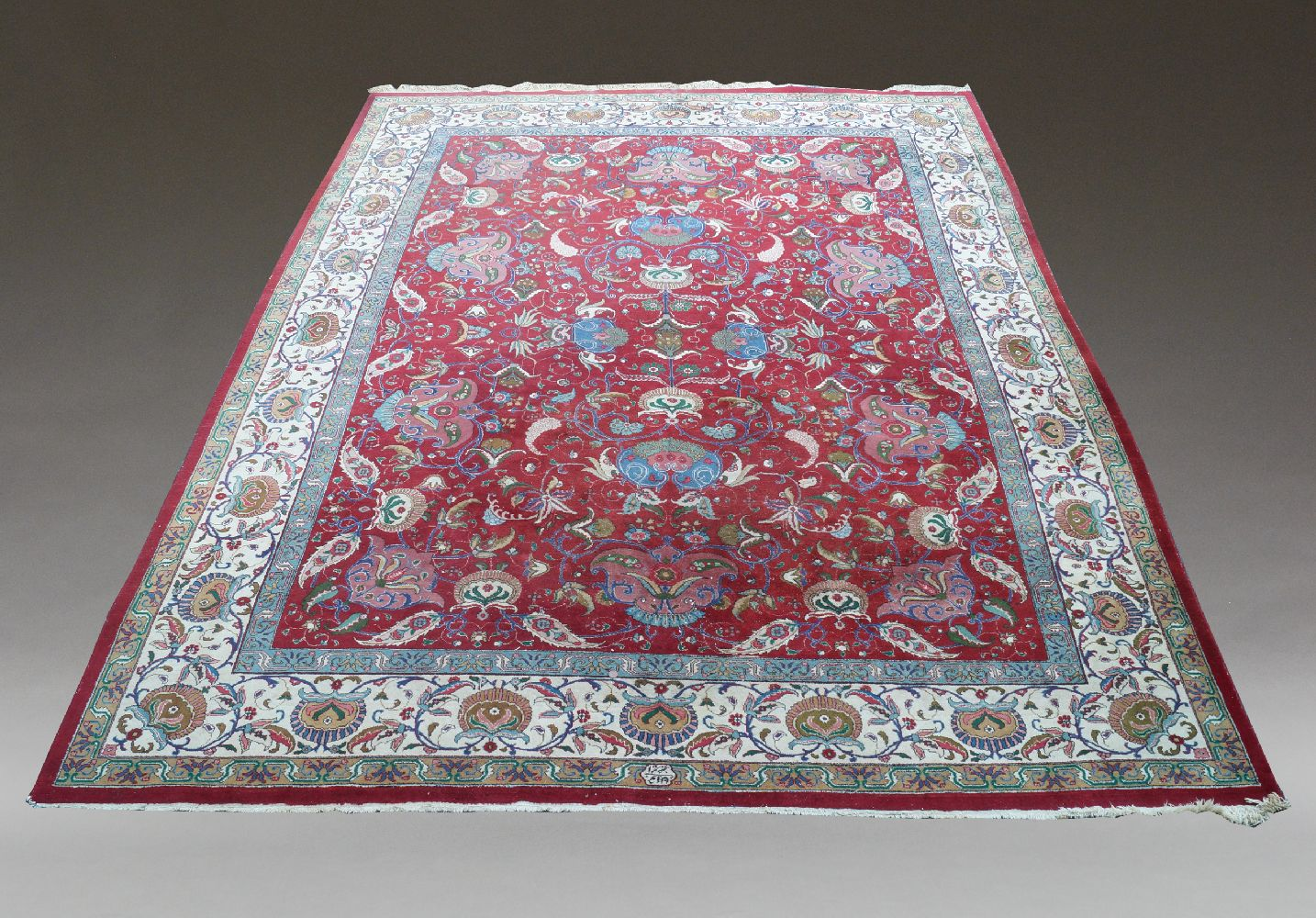 An oriental carpet with all over design of flowering foliate stems in a deep red field and ivory