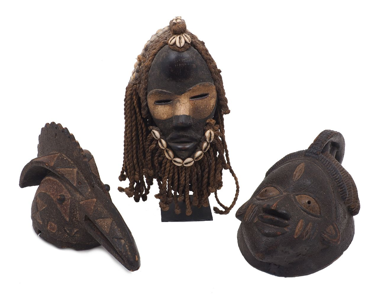 Three tribal masks, comprising: a Yoruba example, 40cm high, a Dan tribal mask with cowrie shells,