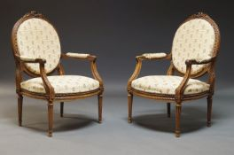 A pair of Louis XVI style fauteuils, first half 20th Century, the oval backs surmount with carved