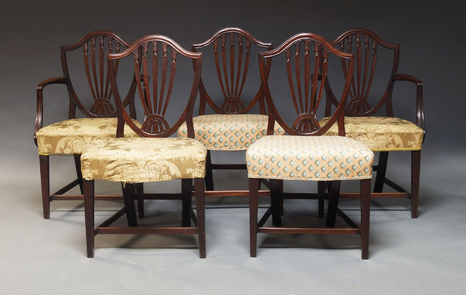 A set of five mahogany Hepplewhite style dining chairs, 20th Century, the shield shaped backrests