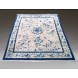 A Chinese carpet, mid to late 20th Century, the blue and white design incorporating vases, sprays of