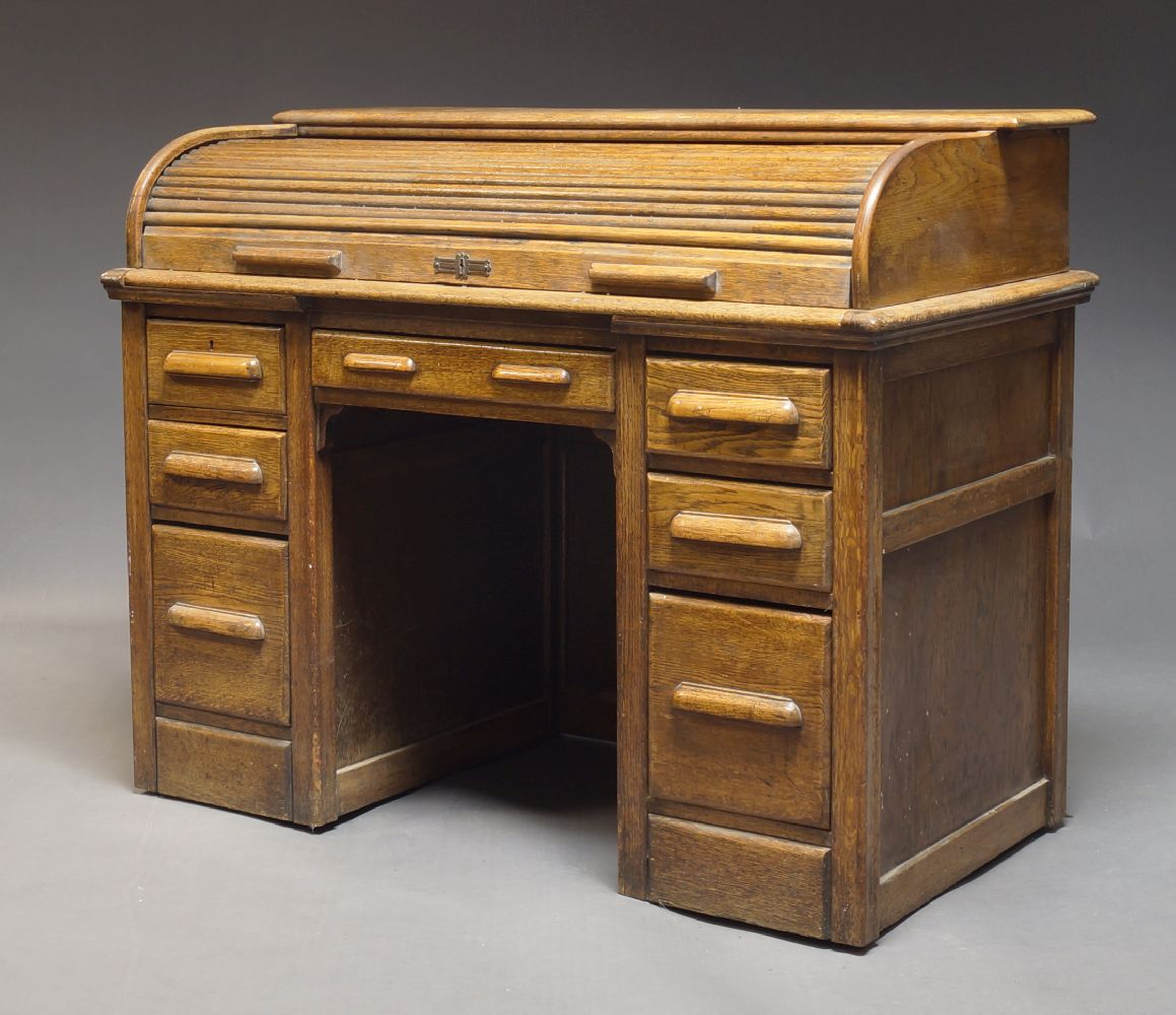 An oak cylinder kneehole desk, with tambour top, enclosing tan leather writing surface and pigeon