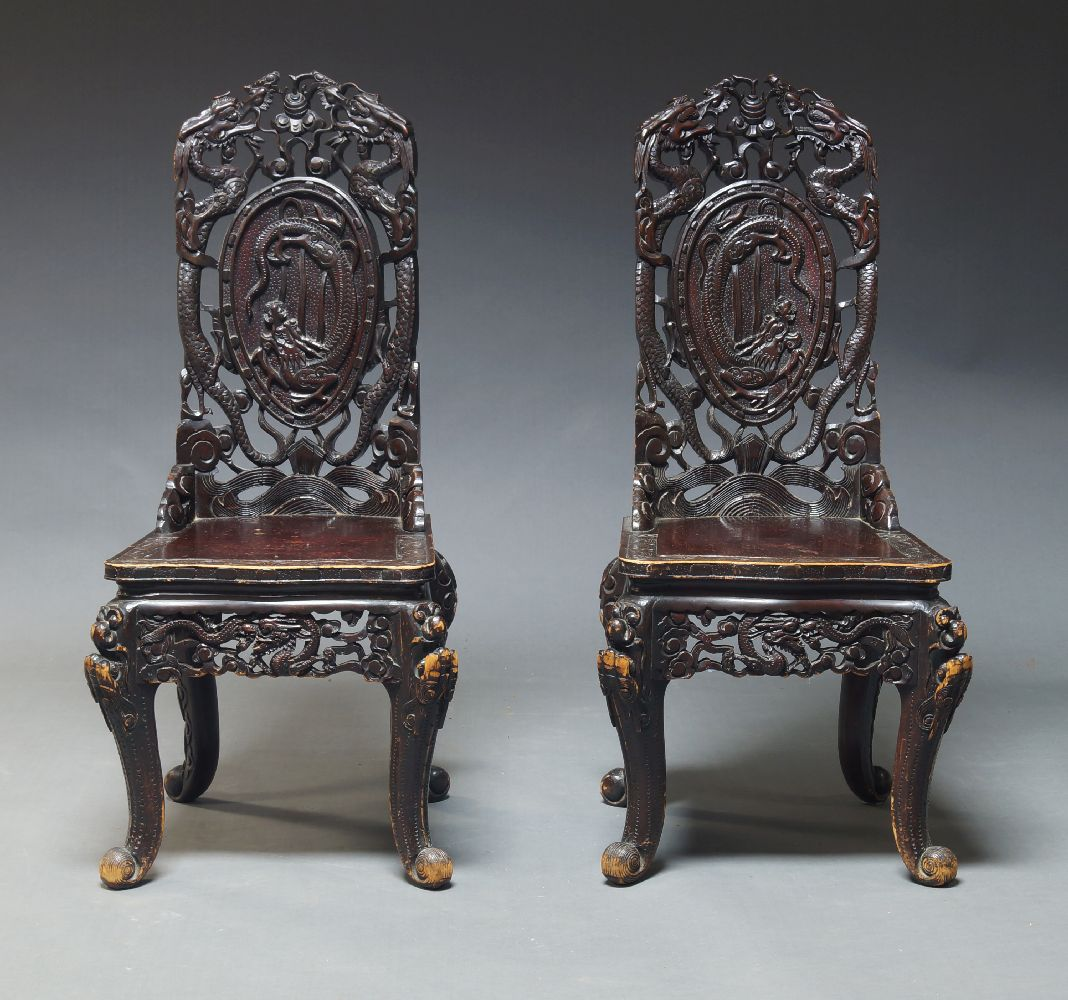 A pair of Chinese carved hardwood chairs, late 20th Century, overall decorated with carved