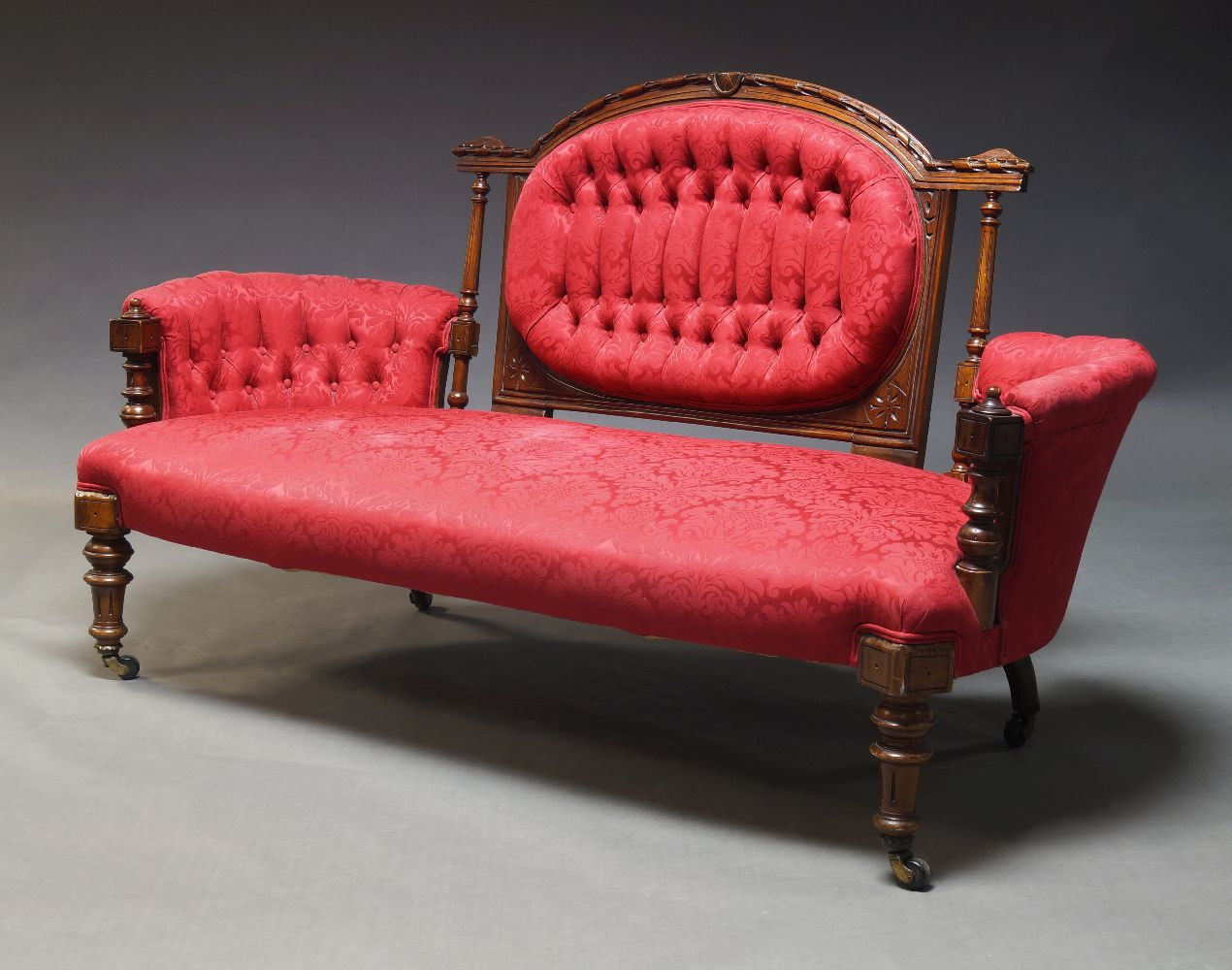 A Victorian walnut framed sofa, the carved back panel with oval upholstered backrest, flanked by