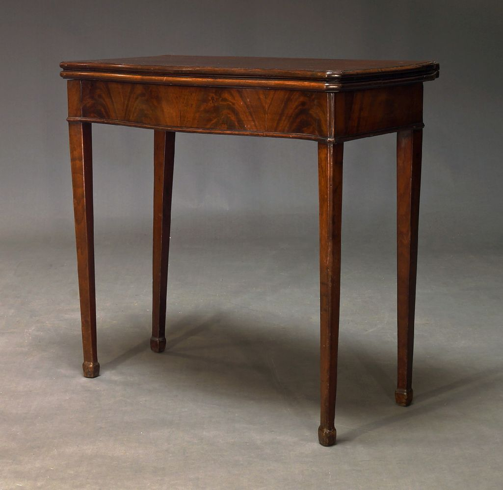 A George III mahogany serpentine card table, the fold-over top enclosing green baize lined playing