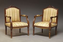 A pair of Louis XVI style stained beech fauteuils, 20th Century, the shaped backs with carved