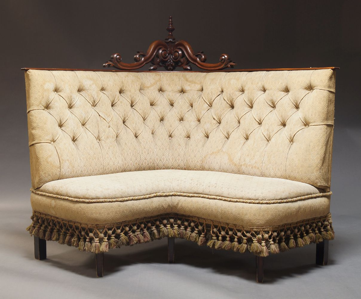 A Victorian corner sofa, the carved and pierced crest with turned finial over foliate and s-scroll