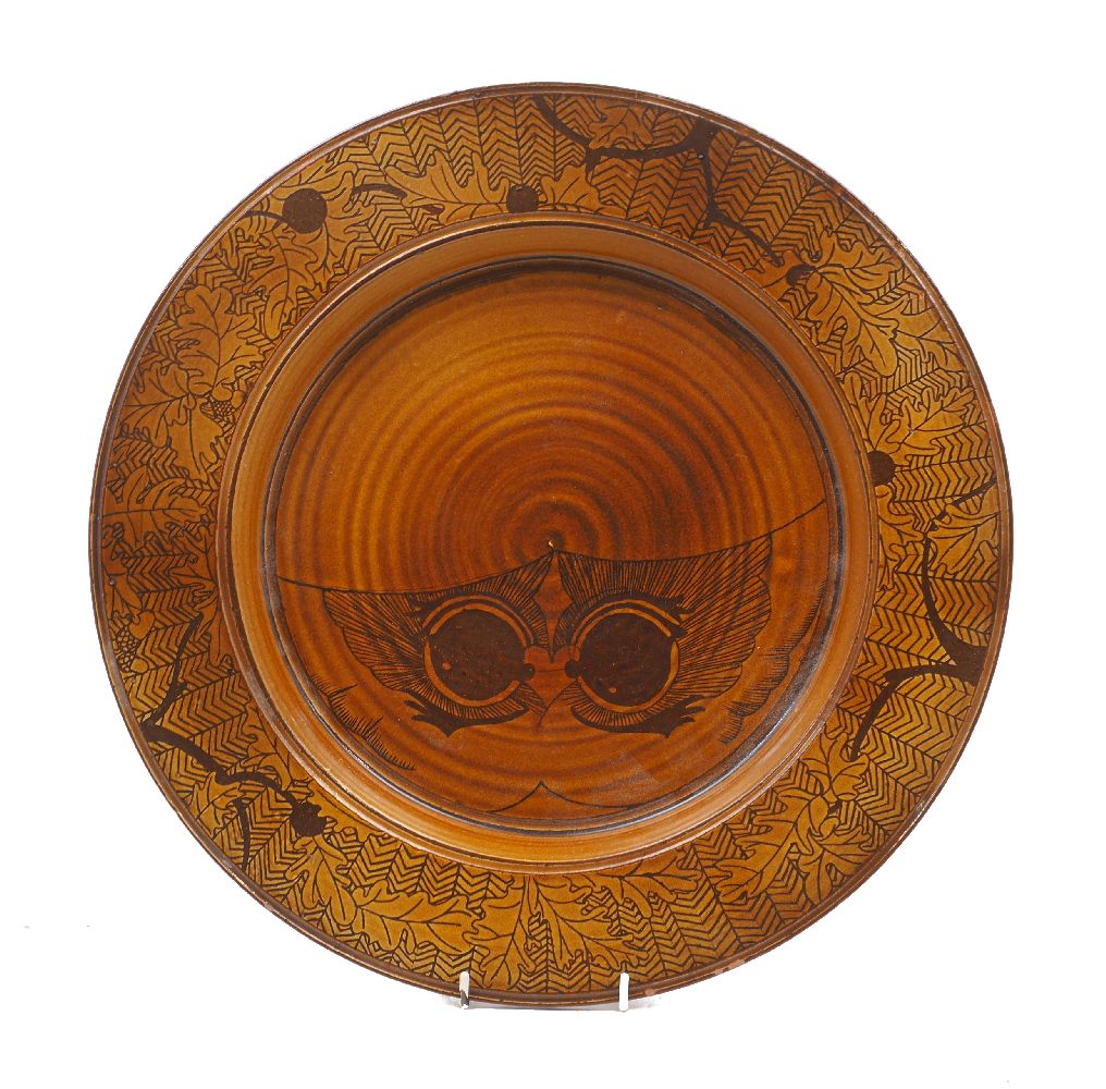 A large studio pottery charger in a brown glaze, with oak leaf and herringbone pattern to the rim,