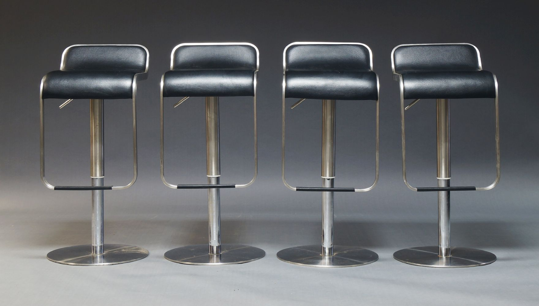 After Shin & Tomoko Azumi, a set of four adjustable bar stools, with black leather seats, on