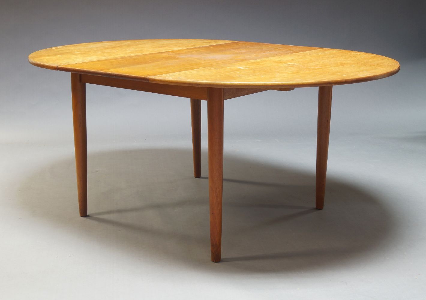 A Danish teak extending dining table, c.1960, the rounded top with central fold out leaf, on