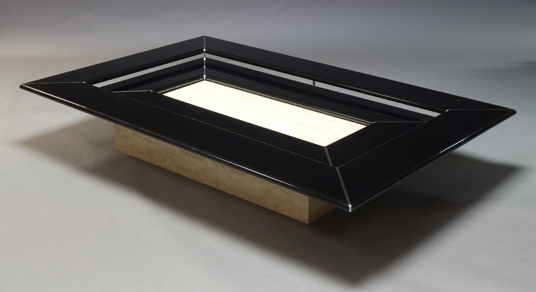 A black lacquered and polished travertine coffee table, c.1980, the rectangular black lacquered