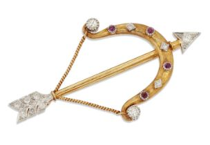 A diamond and ruby brooch, designed as a bow and arrow, the arrowhead and flights set with