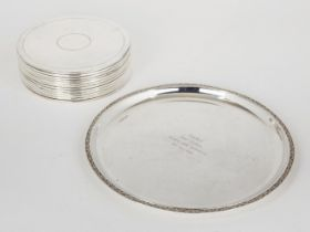 A set of twelve silver plated place mats, of circular form, with ringed decoration and felt