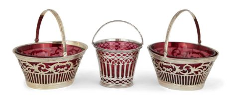 Three Victorian silver sweetmeat baskets with red glass liners, comprising: a pair of oval