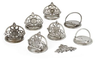 A set of seven silver plated menu holders,19th century, each pierced trefoil section decorated