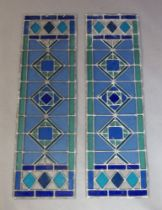 A pair of modern narrow stained glass panels, designed in green and blue glass with diamond motif to