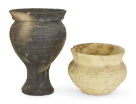 A grey ware pottery vessel with globular body, wide everted rim, set on an integral pedestal base,