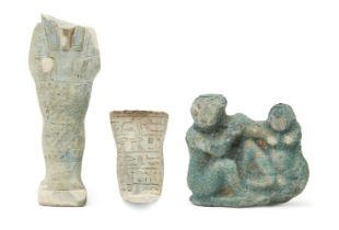 A fragmentary Egyptian blue glazed composition shabti of typical mumiform, holding two hoes, with