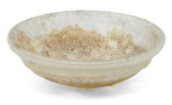 A Roman clear glass dish and a lid, 2nd-4th century AD, the first of deep form with heavy