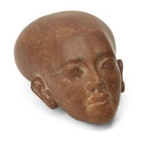 An Egyptian style brown quartzite head of an Amarna style princess, with elongated skull and defined