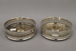A pair of silver mounted bottle coasters. 13.5 cm diameter. 10.1 troy ounces total weight.