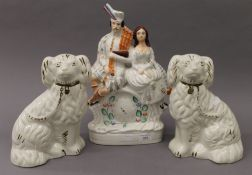 A pair of Staffordshire dogs and a Staffordshire flatback clock group. The latter 36 cm high.