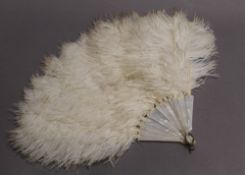 A vintage ostrich feather and mother-of-pearl fan. 38 cm long.