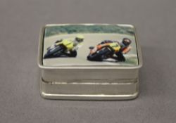 A silver pill box depicting motorbikes. 3 cm wide.