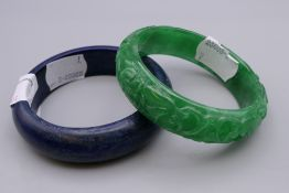 A Chinese carved jade bangle and another. The former 7.25 cm diameter.