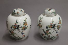 A painted pair of 19th century famille verte porcelain ovoid vases and covers. 27 cm high.