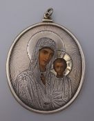 An antique Russian silver clad icon pendant. 8 cm high. 59.6 grammes total weight.