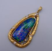 A large 18 K gold opal and diamond pendant. 9 cm high. 70.4 grammes total weight.