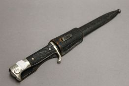 A German dagger in scabbard. 34 cm long.