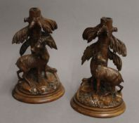 A pair of Blackforest carved wooden stands, each carved with a chamois deer. The largest 23.