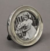 A small silver circular photograph frame. 7 cm diameter.