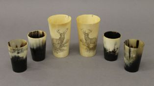Six vintage horn beakers, two carved with a stag. The largest 11.5 cm high.